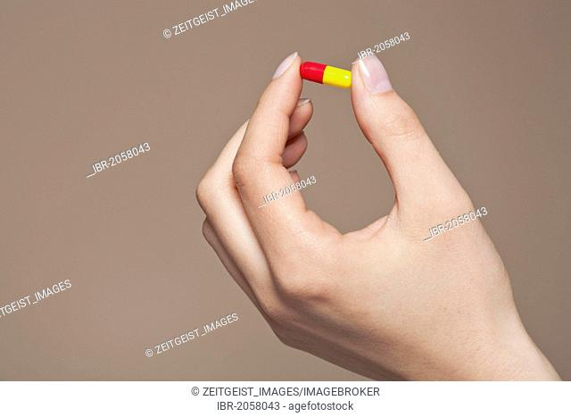 Hand of a young woman holding a pill, capsule between her fingers
