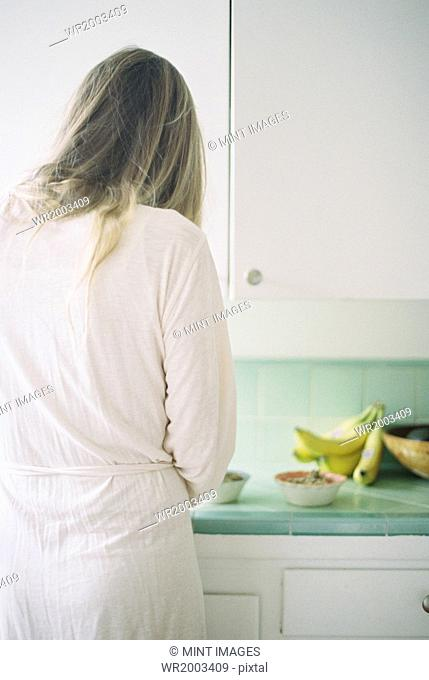 Rear view of a woman standing in a kitchen, preparing breakfast