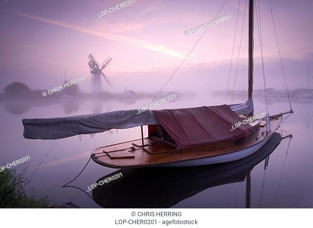 England, Norfolk, Thurne, A misty view across the water to Thurne Mill at sunrise